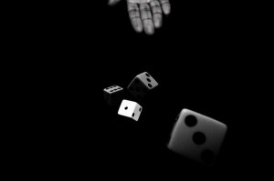 hand-throwing-a-pair-of-dice-in-black-and-white-anya-brewley-schultheiss